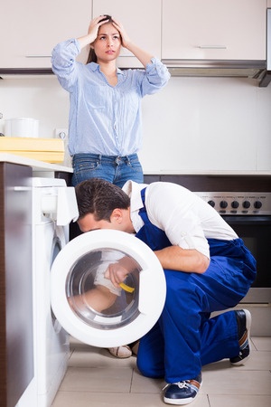 Young housewife and repairman near broken washing machine in domestic interior Reklamní fotografie