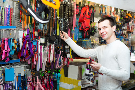 petshop: Portrait of young man choosing collars and leads in petshop Stock Photo