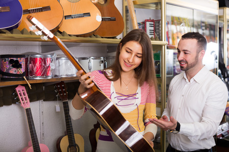 selecting: Happy couple selecting acoustic guitar in music instruments shop