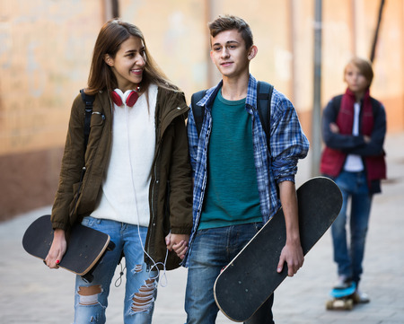 unfaithfulness: Jealous teen and his smiling spanish  friends after conflict outdoors