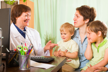 general pediatrician: Smiling aged female pediatrician doctor examining two kids in clinic