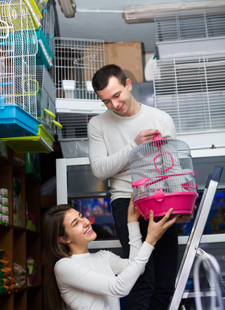 19's: Couple of ordinary customers buying cage for bird in shop and smiling