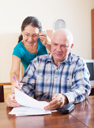parsimony: mature couple reading documents at home Stock Photo