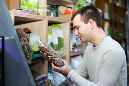 petshop: Portrait of positive guy selecting vet food in petshop
