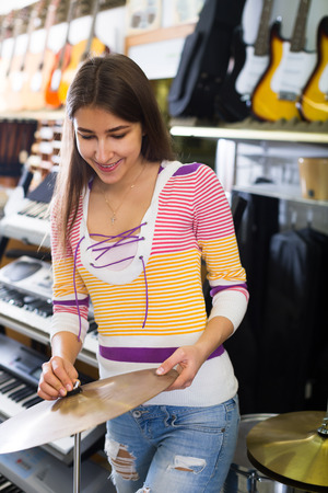 selecting: Happy girl selecting drums and accessories in music shop