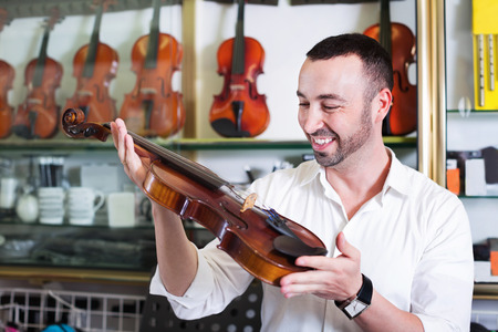 violins: Young man with beard purchasing traditional violins in store