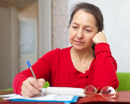 demure: serious mature woman fills in documents at home Stock Photo