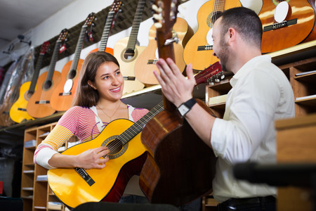 25s: Smiling girl and handsome guy playing the guitars in shop Stock Photo