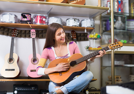 18's: Smiling female customer trying to play guitar in store