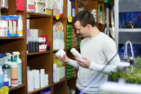 petshop: Ordinary male customer buying flea treatment and shampoo in petshop