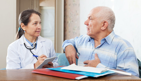 complaining: Senior man complaining to doctor about heartache