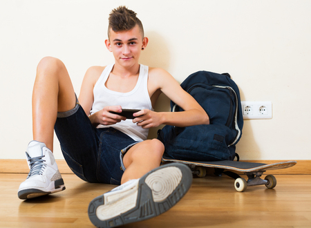 16s: Happy young teenager burying in mobile phone and social networking indoors Stock Photo