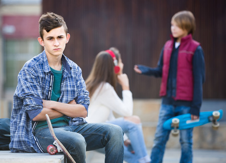 16s: Jealous teen and his young american  friends after conflict outdoors Stock Photo