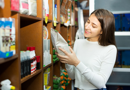 19's: Ordinary female customer buying dry food for pets in shop
