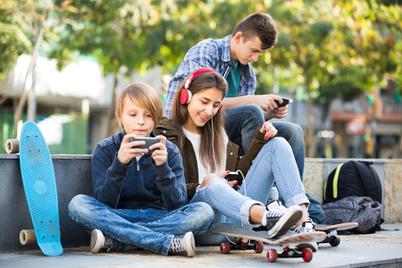 16s: Group of ordinary teenagers in casual relaxing with mobile phones outdoor. Focus on girl