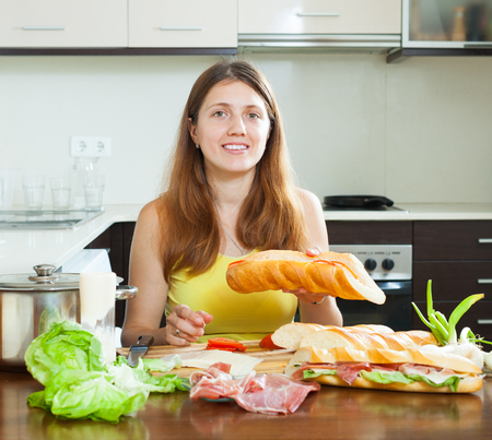 kitchen spanish: woman cooking spanish sandwiches (bocadillo) with vegetables and  hamon in home kitchen