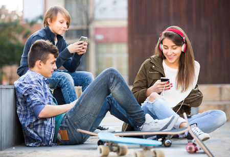 16s: Three teenagers with smartphones and skateboards  in autumn day outdoors
