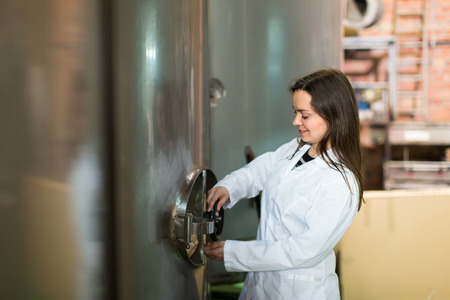 technologist: Female technologist in white overall near tub filled with olive oil in manufacturing environment