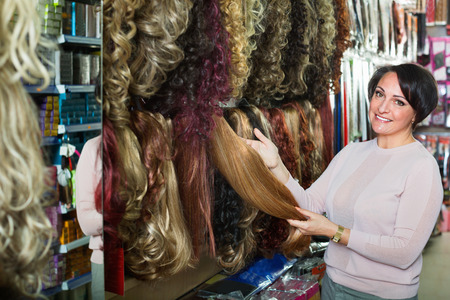 chignon: Positive charming  middle aged woman purchasing hair extension in salon