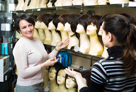 peruke: Ordinary women buying modern periwigs and smiling in shop