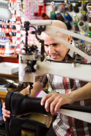 broach: Professional elderly shoemaker stitching footwear on machine in shoe atelier Stock Photo