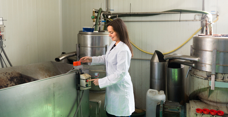 full metal jacket: Adult girl with flexible tubing and pot at olive oil industry at factory