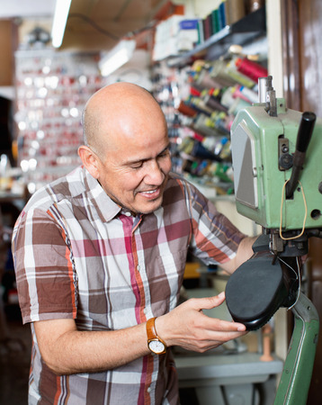 broach: Mature efficient positive smiling workman sewing leather boots on stitch lathe in workshop Stock Photo