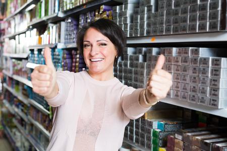 tinte de cabello: joven mujer de elegir la caja de tinte para el cabello en la tienda de la sonrisa