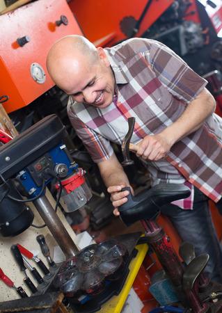 replacing: Mature shoe repairman replacing heeltaps on shoe at workshop and smiling Stock Photo