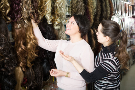 chignon: Customers buying clip-in natural hair extension at store Stock Photo