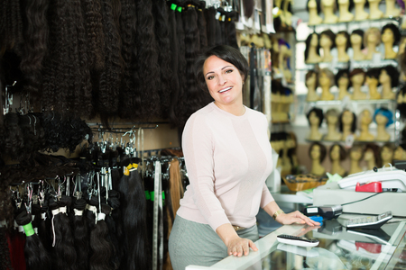 tresses: Ordinary female assistant selling natural hail ponytails, tresses and wigs
