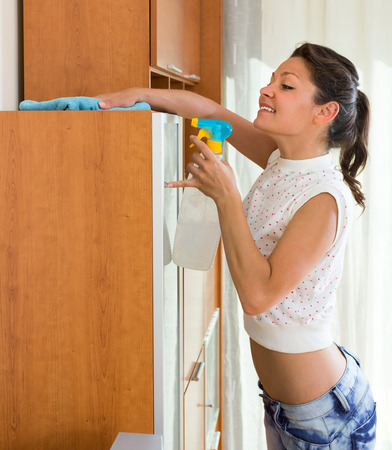 shred: Smiling young housewife cleaning cabinet with sprayer and shred