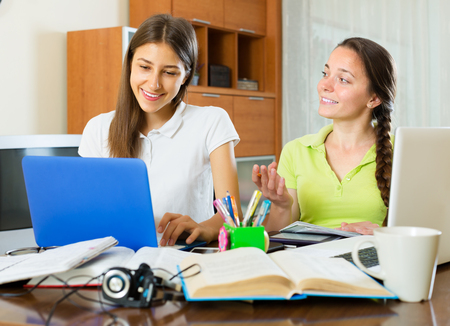 erudition: Smiling young college student girls studying at home with books and computers Stock Photo