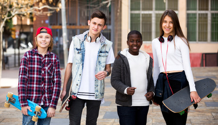 blabbing: Happy group teens with skateboards posing in town square