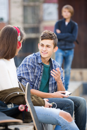 morose: Jealous teen and his smiling russian friends after conflict outdoors