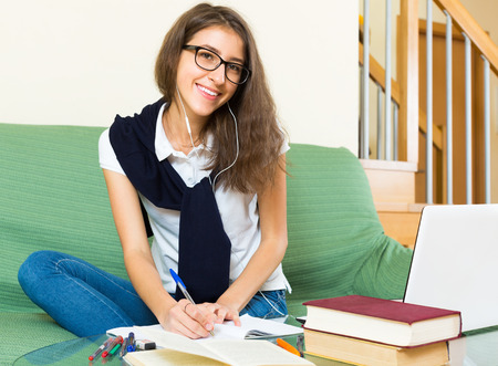 erudition: Smiling teenager girl in glasses doing homework on the couch at home Stock Photo