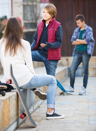 unfaithfulness: Jealous teen and his happy american friends after conflict outdoors Stock Photo