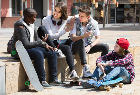blabbing: girl and three american  boys hanging out outdoors and discussing something Stock Photo