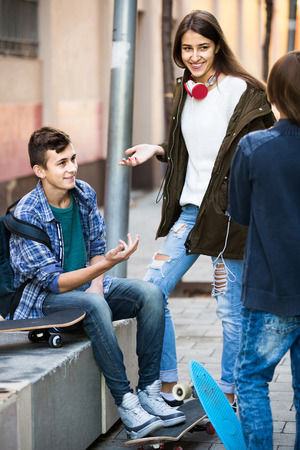 blabbing: Group of happy teenage friends chatting and having fun outdoor