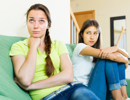 deplorable: Two unhappy woman friends sitting on the coach discontent and having an argument