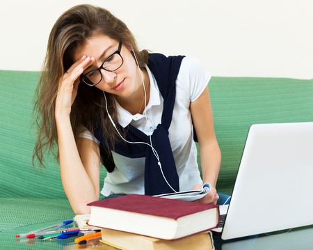 erudition: Unhappy young girl at home behind her laptop