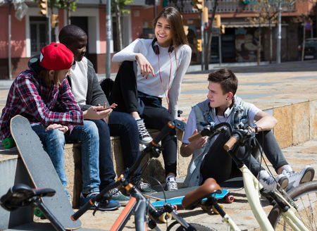 blabbing: positive girl and three smiling boys hanging out outdoors and discussing something