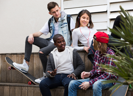 blabbing: Happy american teens spending time together and talking in sunny day Stock Photo