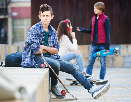 sullen: Upset male teen sitting aside of girlfriend talking with boy