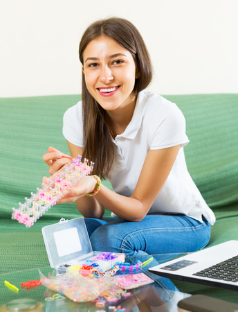 pleasure craft: Smiling girl makes braslets with elastic rainbow loom bands Stock Photo