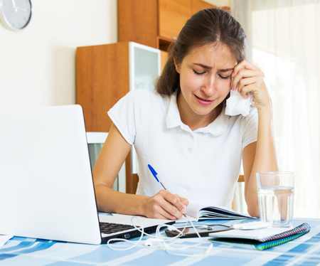 armenian woman: Crying female college student study sitting at a table in the living room Stock Photo