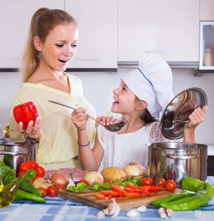 vegeterian: young american mom and little daughter cooking vegeterian dish indoors