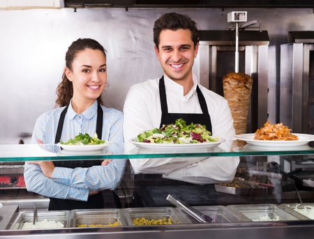 restaurant staff: Positive adult restaurant staff posing at kebab counter and smiling