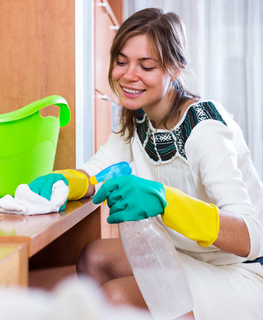 cleanup: Happy young woman doing regular clean-up and smiling indoors Stock Photo