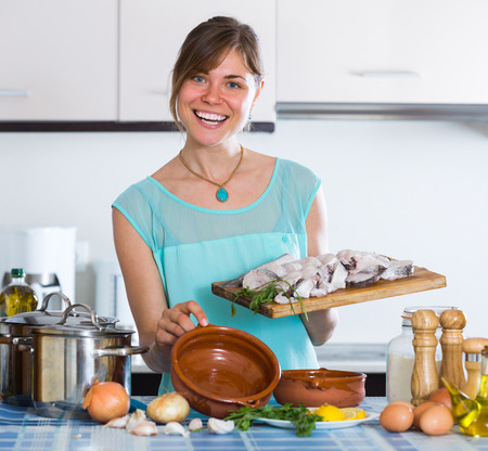 hake: Cheerful smiling young housewife cooking hake in ceramic pot at home Stock Photo